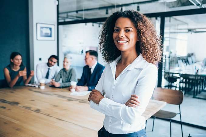Shot of a beautiful african-american businesswoman standing with arms crossed in front of her team in board room. Multi-ethnic group of business people on meeting in conference room.